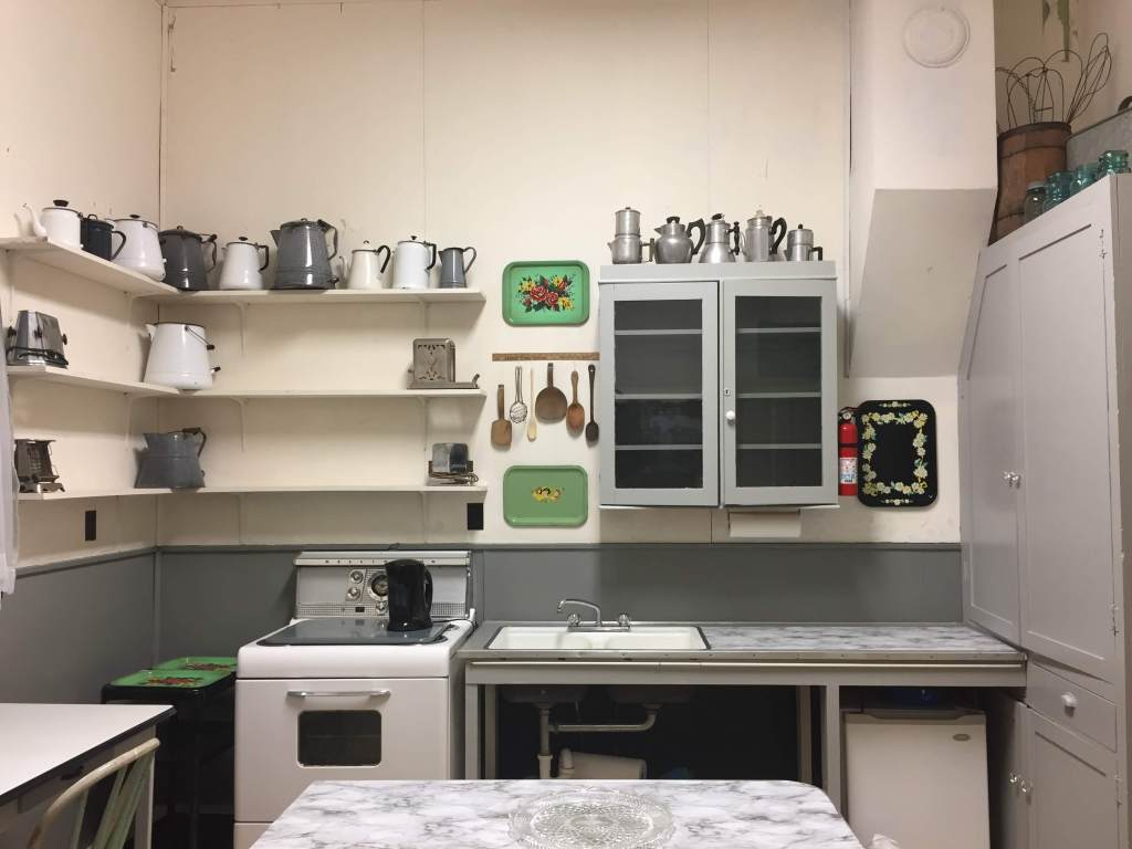 The former kitchen, now a more functional space, with cleared shelves and tables and new gray walls.